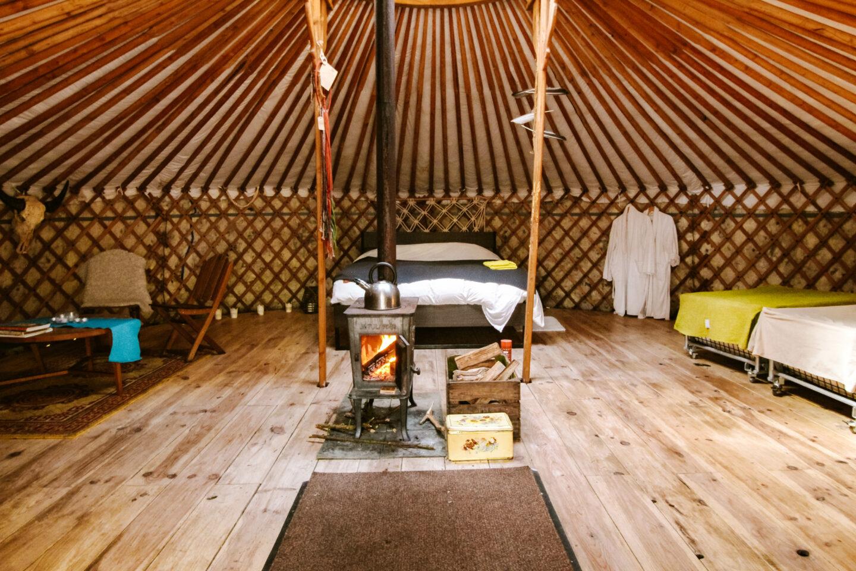 slapen in een yurt bij the yurt project de binnenkant van de Serenity yurt met houtkachel
